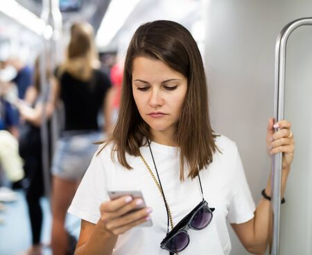 Focused girl using smartphone in subway wagon