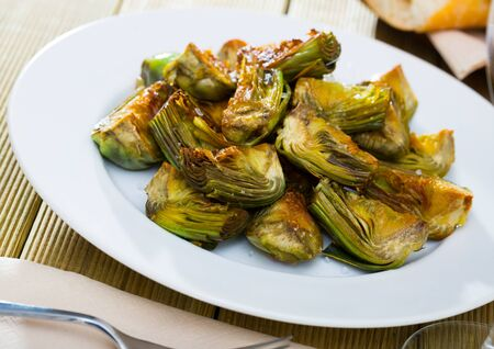 Appetizing roasted in oil artichokes served on plate