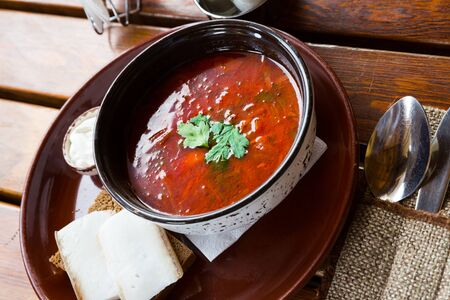 Ukrainian borsch red soup with pork and sour cream , served with bread and salo Imagens