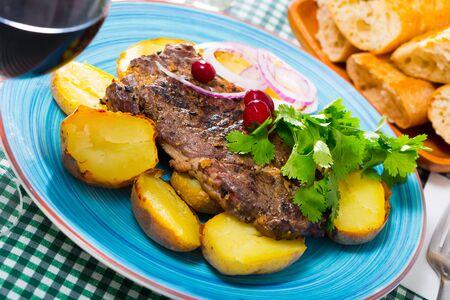 Gustosa bistecca di manzo con patate al forno servita al piatto con verdure Archivio Fotografico