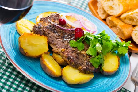 Tasty beef steak with baked potatoes served at plate with greens Stock Photo