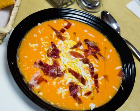 Delicious Spanish pureed cold soup from tomatoes and bread (Salmorejo) garnished with grated boiled eggs and sliced ham