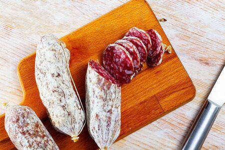 Traditional italian dry cured sausage Salamini italiani alla cacciatora on wooden table Imagens