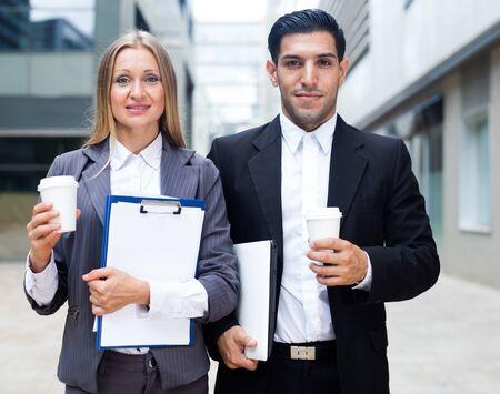 Biznesmen i jego koleżanka w garniturze stoją z folderem i kawą w pobliżu biura. Zdjęcie Seryjne