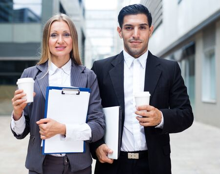 Businessman and his woman colleague in suit are standing with folder and coffee near the office. Banco de Imagens
