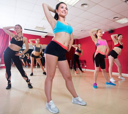 Happy smiling females are practising rouch movement in jazz dance in fitness-gym.