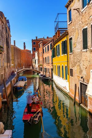 Traditional Venetian gondola with tourists plying in narrow canal of Venice, Italy Standard-Bild
