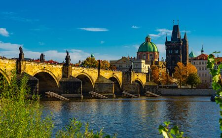 Picturesque view of Prague on bank of Vltava river with medieval arched Charles Bridge and Old Town Bridge Tower on autumn day, Czech Republic 版權商用圖片