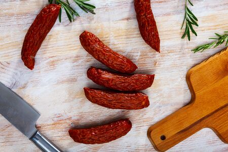 Tasty smoked ham sausages with spices on wooden background. Traditional Czech meat product