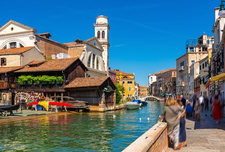 Picturesque Venice cityscape with Grand canal, moored boats, gondolas and ancients colorful buildings on banks of canal