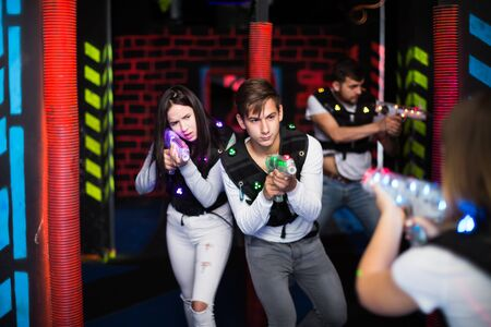 Modern guy and girl aiming laser guns at other players during laser tag game in dark room