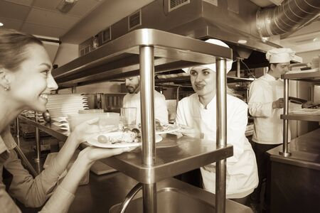 Chef of restaurant with team of cooks busy to preparing food for they client