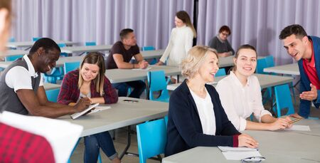 Friendly adult people communicating during joint training in classroom