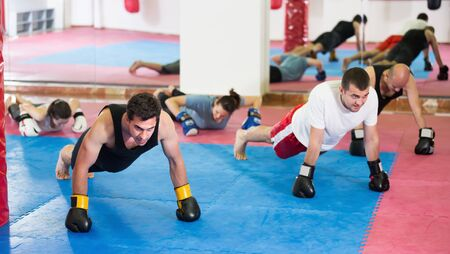 Group of men training together in the boxing hall