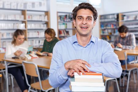 Portrait of delighted adult man with stack of books in hands in public library Stock fotó