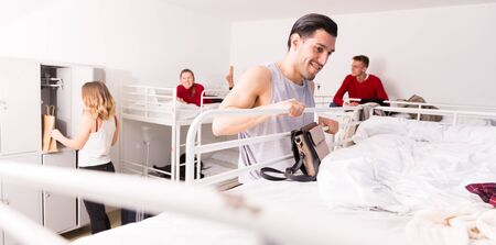 Young man climbing up to top bunk of bunk bed in hostel dorm Stock Photo