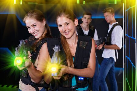 Two sporting women with laser pistols in foreground and two guys in background in laser tag room