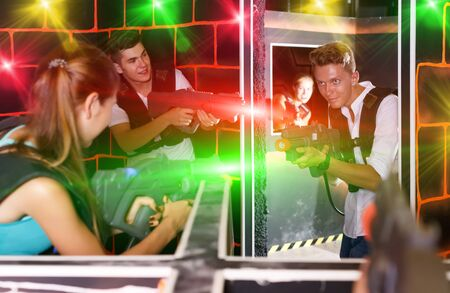 Group of young people with plastic laser pistols enthusiastically playing laser tag