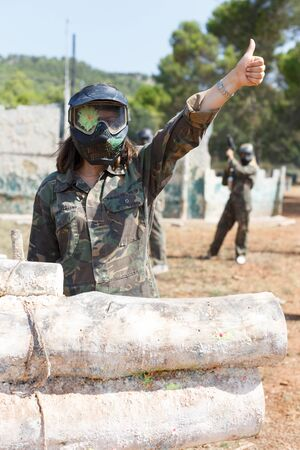 Female paintball player in camouflage and black mask with paint from hit markers