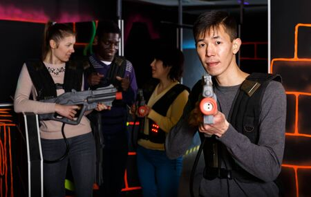 Focused adult Chinese man wearing special vest and holding laser gun ready for lasertag game with friends