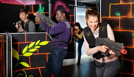Portrait of young man and woman with the laser pistols playing laser tag at dark labyrinth Foto de archivo