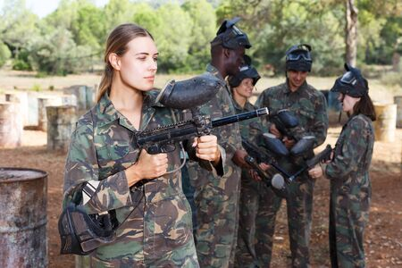 Young female paintball player in camouflage standing with gun before playing outdoors