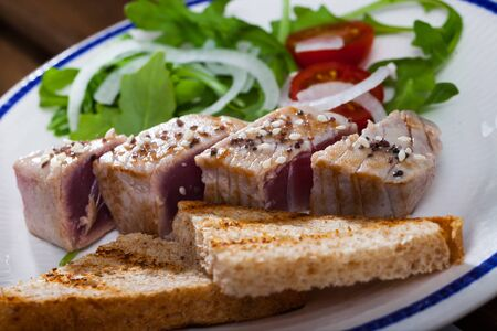 Tataki (tuna fillet) served with toasts and greens on plate