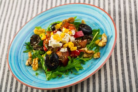 Healthy arugula salad with fresh vegetables, soft cheese, walnuts and corn kernels served on colored ceramic plate