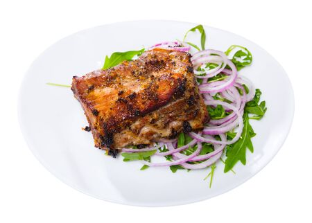 Grilled pork ribs rack garnished on white plate with arugula and red onion. Isolated over white background