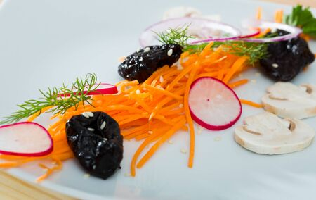 Image of salad from fresh carrot, radishes and prunes served at  plate with greens