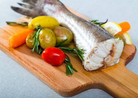 Cod baked in rustic style. Recipe: better to take cod tail 250 gr, rub with salt, pepper. Bake in oven 20 minutes at 220 gr. Garnish with boiled potatoes, carrots, fresh tomatoes, greens and lemon Banque d'images - 135904185