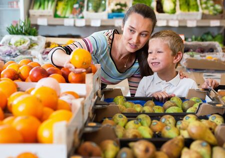 Portrait of happy cheerful positive friendly woman and her little son choosing oranges at shop