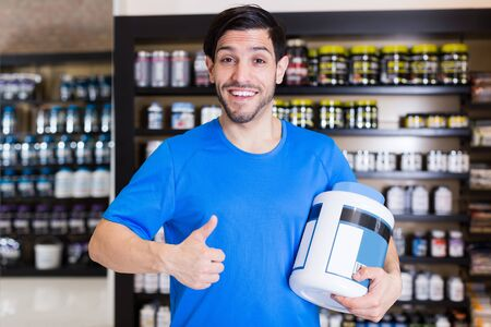 Young  sportman  keeping thumb up and big pot of sport nutrition products in shop