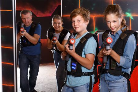 Positive teenage boy and sister aiming laser guns  during laser tag game with parents in arena