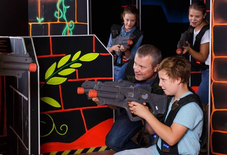 Cheery teenager boy and his father aiming laser guns at other players during laser tag game indoors Фото со стока