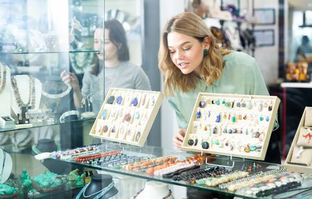 Interested girl behind glass of showcase looking at natural gemstone jewellery on shelves of jewelry boutique