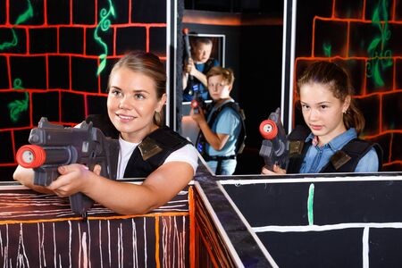 Modern young cheerful woman and teen girl with laser pistols playing laser tag in dark labyrinth