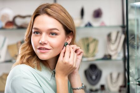 Stylish young female client trying on sterling silver earrings with green malachite stone in boutique of jewelry