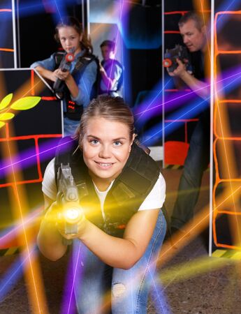 Portrait of excited woman holding laser gun in arena, playing laser tag game with family