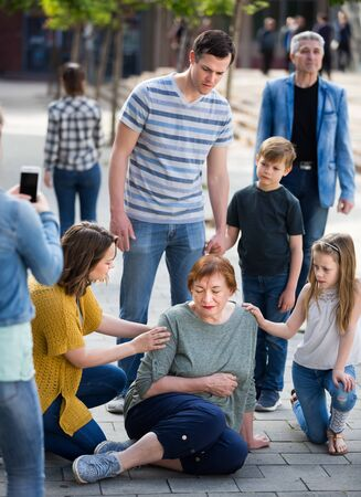 People helping sad grandmother with pain in heart outdoor