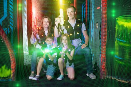 Modern young parents and children with laser pistols posing together in bright beams in laser tag labyrinth