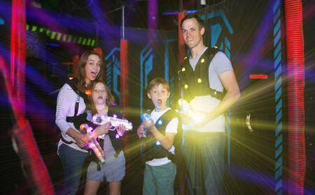 Modern young parents and children playing laser tag in dark labyrinth in bright beams of laser pistols