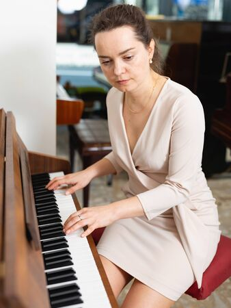 Pretty woman in evening dress playing piano