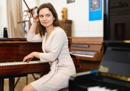 Attractive young woman chooses pianoforte in a record store