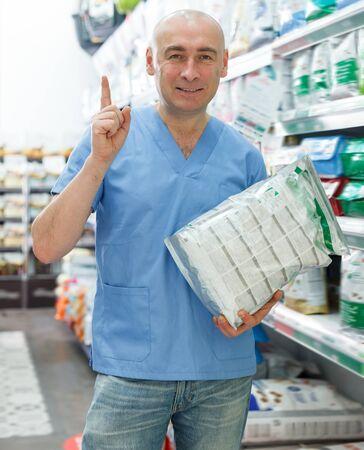 Happy man veterinarian seller with pet dry food standing near shelfs  in pet store