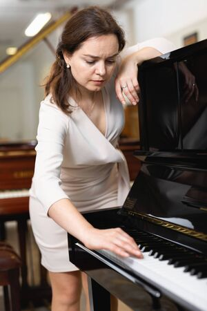 Young woman buys a piano in a music store Zdjęcie Seryjne