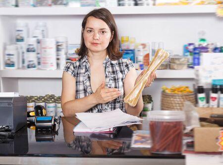 Blije vrouwenverkoper die met documenten en goederen in dierenwinkel werkt Stockfoto