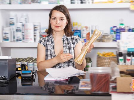 Glad woman seller working with documents and goods in pet store