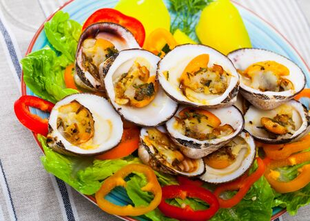 Delicious baked in oven Dog cockles (bivalve shellfishes) served with greens and vegetables