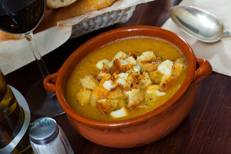 Vegetable soup with croutons and cheese in a clay plate Stockfoto